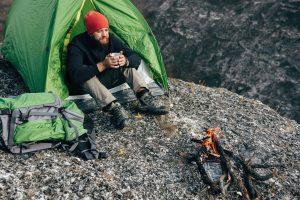 mężczyzna pod namiotem z kubkiem
